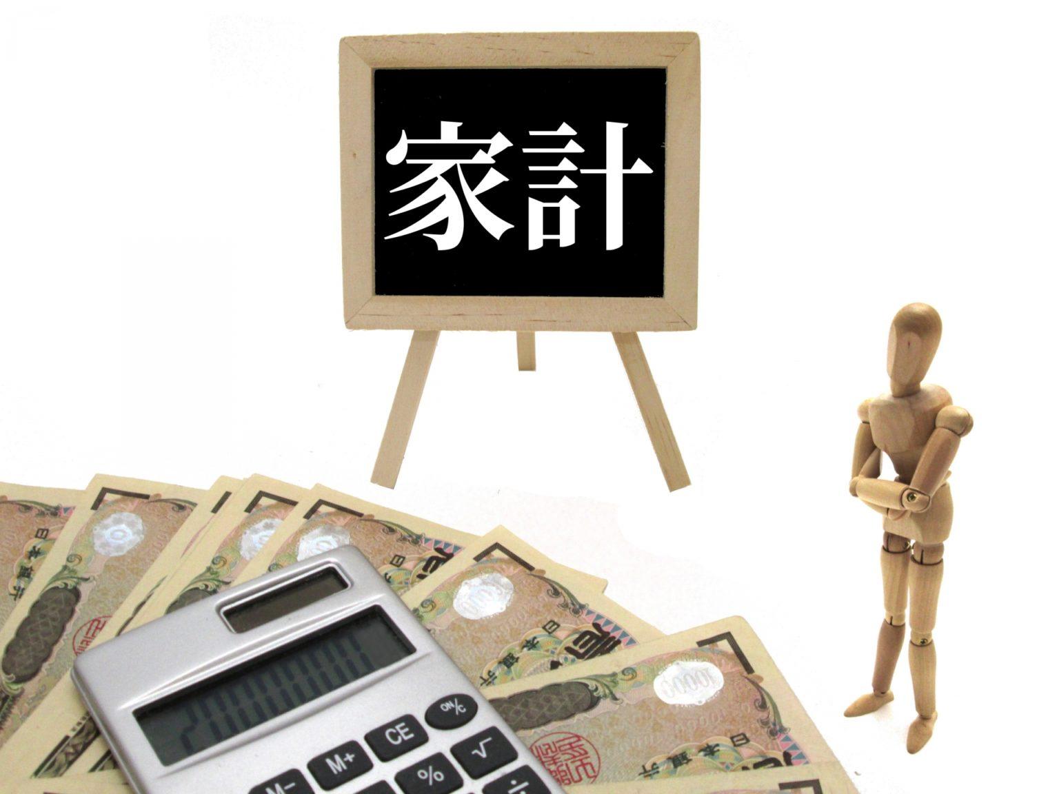 家計看板とお金と電卓をみて考える木製人形