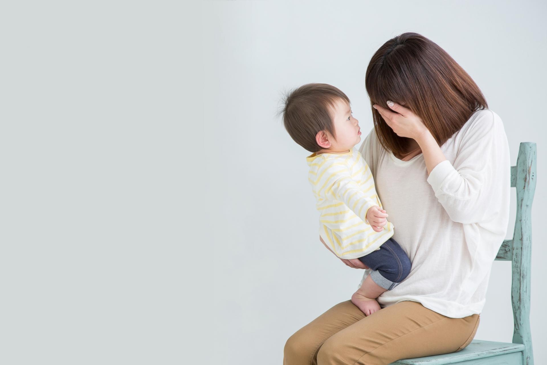 座って赤ちゃんを抱っこして泣いている女性
