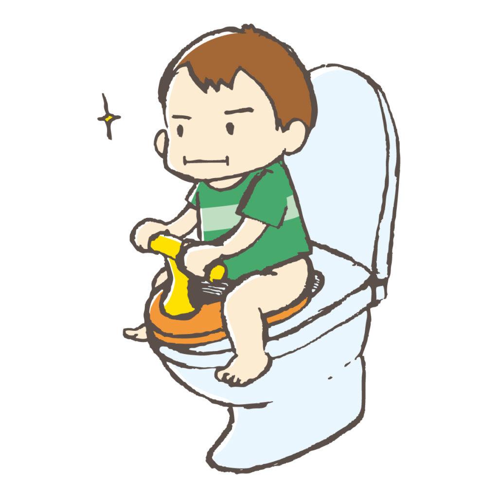 男の子がトイレの補助便座にまたがっている