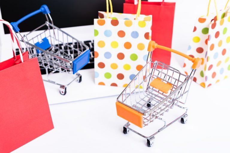 パソコンと小さい買い物カートとショッピングバッグ